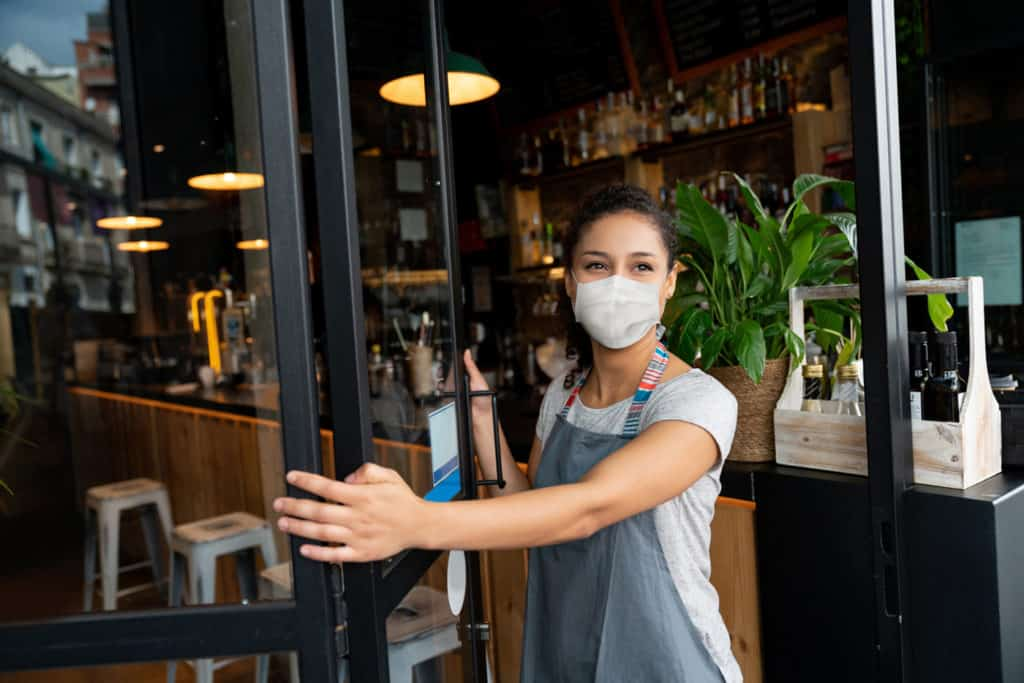 Woman with face mask opening restaurant door